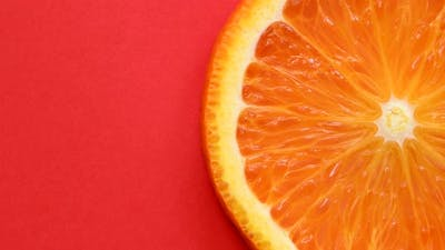 Slice of orange rotating close-up on red background
