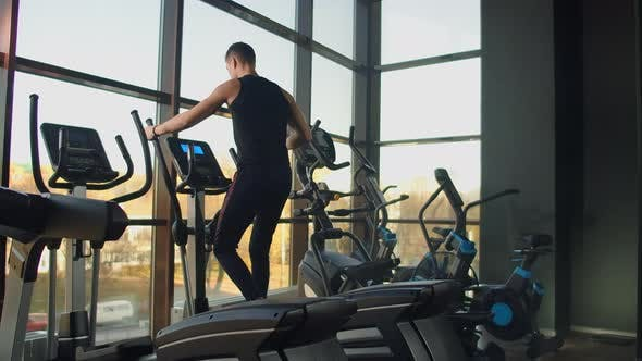 Thumbnail for Portrait Fitness Man Warm Up Before Training on Elliptical Cross Trainer in Gym Club. Close-up Male