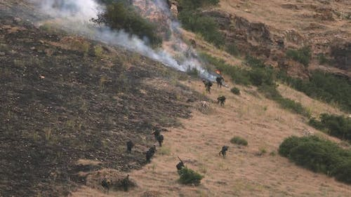 Zoomed view of firefighters working to extinguish wildfire