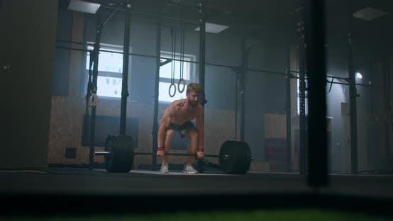 Breiter Schuss von jungen kaukasischen Extreme Gewichtheben Athlet Mann, der mit schwerer Langhantel in