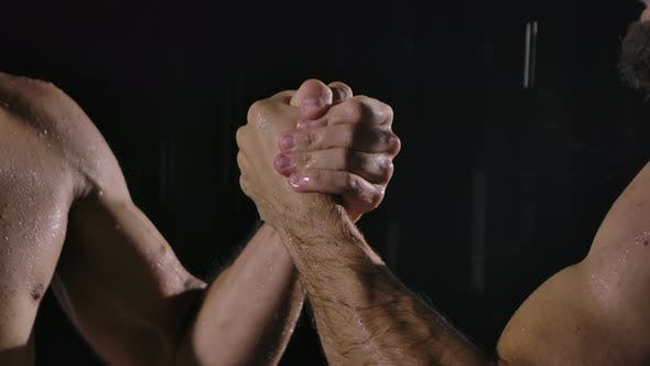 Thumbnail for Handshake of Two Muscular Men on a Black Background Among Raindrops and Many Splashes. Slow Motion