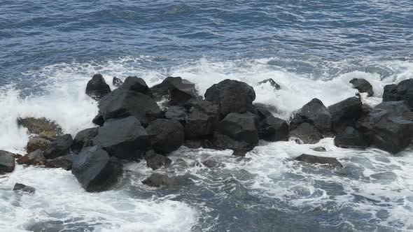 Thumbnail for Sea waves hitting against big rocks and breaking into foam, water slow motion