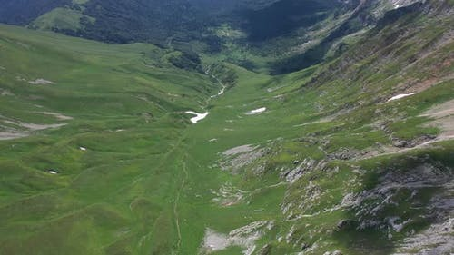 Flying Backward Over a Mountain Valley in Mountains of Adygea on Summer Day. Green Trees and Bushes