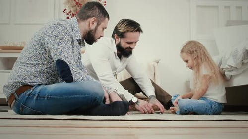Male couple and five-year-old girl play a board card game