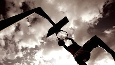 Basketball player dunking basketball and scores in basket