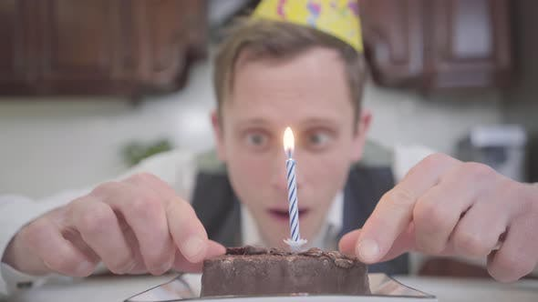 Thumbnail for Portrait of a Funny Young Man in Birthday Hat Sitting in Front of a Small Chocolate Cake in the