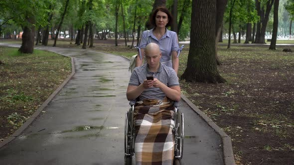 A Woman Is Leading a Young Man with Oncology in a Park in a Wheelchair