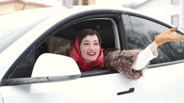 Stylish Woman Looking Out of Car Window in Winter
