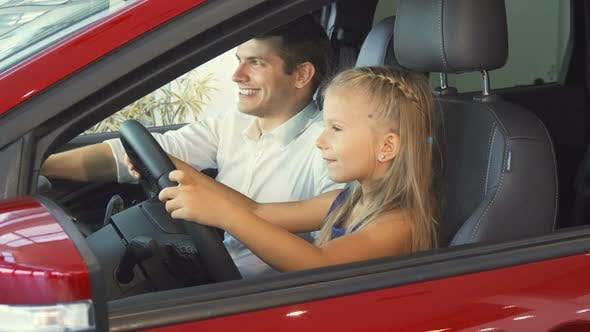 Thumbnail for A Little Girl Is Sitting with Her Dad in the Car and Pretending To Turn the Steering Wheel