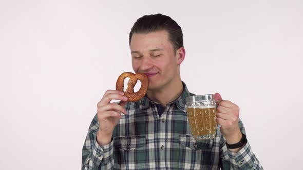 Thumbnail for Cheerful Young Man Holding Mug of Beer, Smelling Delicious Pretzel