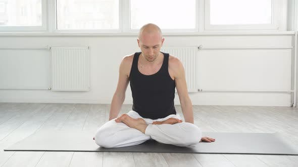 Professional Yoga Man Sits on Mat on Floor Training Correct Yoga Breathing