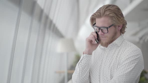Thumbnail for Handsome Sad Man in Glasses Standing in a Light Comfortable Office Talking By Cell Phone. Handsome