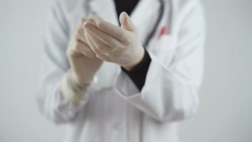Scientist Female Putting Gloves in the Lab. Coronavirus Disease Prevention