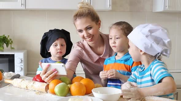 Thumbnail for Young Woman with Children Watching Baking Recipe on Smartphone