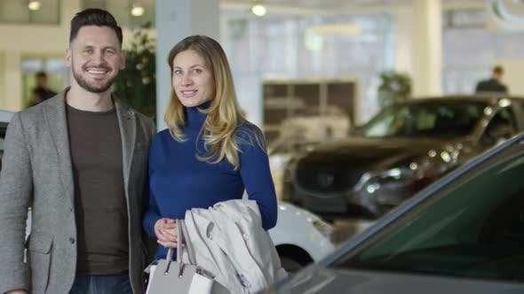 Cover Image for Happy Couple Posing at Car Dealership