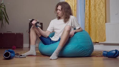 Confident Concentrated Young Retro Man Using Dumbbell Sitting on Bag Chair at Vintage 80s or 70s