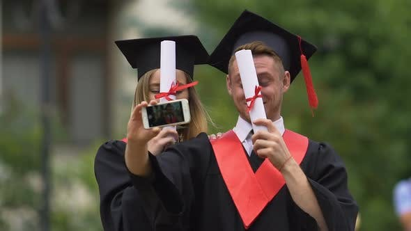 Thumbnail for Happy Man and Woman in Academic Caps and Gowns Filming Video on Smartphone