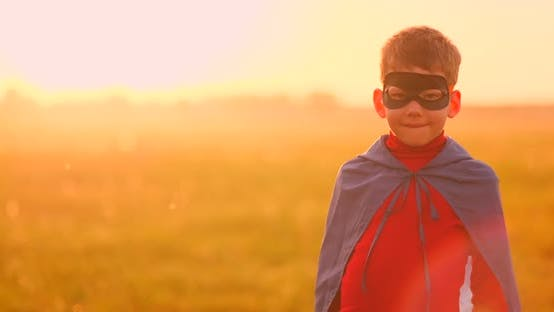 Thumbnail for Portrait of a Boy in a Mask of a Super Hero Looking at the Camera Standing in a Field at Sunset.