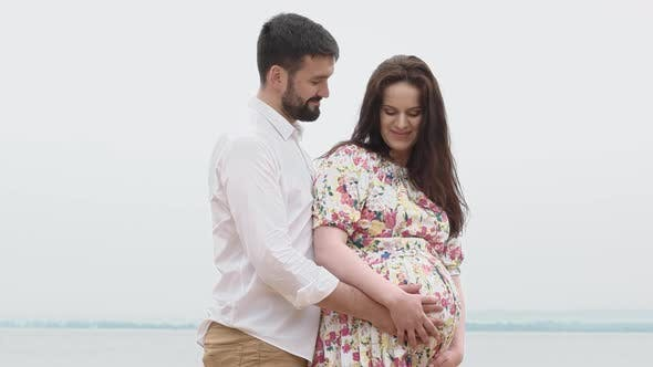 Thumbnail for Romantic Couple In Sunny Summer Day embracing and cares pregnant woman belly