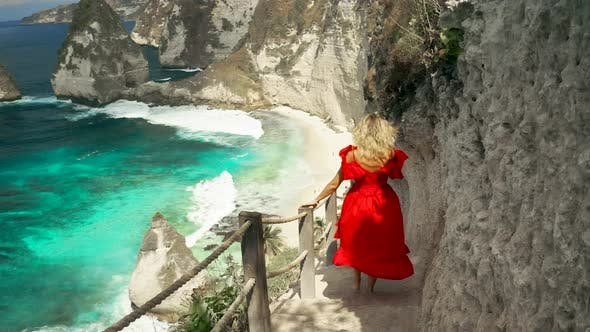 Thumbnail for Young Woman in Red Dress Hikes Down Steep Path To Beautiful Diamond Beach in Nusa Penida Island
