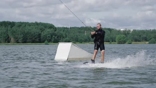 Wakeboarding on the Lake Near Forest, Sportsman Surfs on Water, Ride on Wakeboarding Board, Water