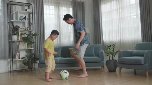 Happy Asian Father And His Son Playing Soccer In Living Room