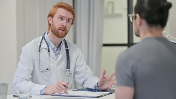 Redhead Male Doctor Discussing Medical Report with Patient