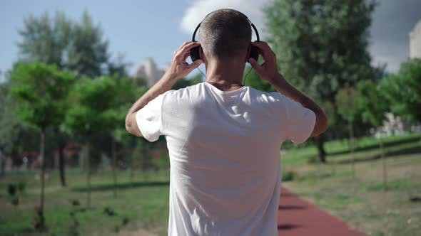 Thumbnail for Back View of Adult Sportsman Putting on Headphones and Start Jogging Along Running Track Outdoors
