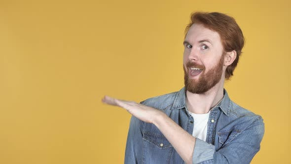 Thumbnail for Redhead Man Pointing with Finger on Side, Yellow Background