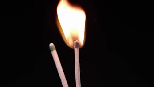 Slow motion of blue laser pointer lighting a match