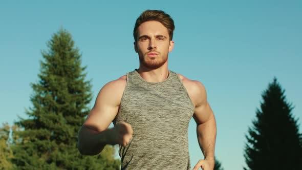Thumbnail for Sport Man Running in Park on Blue Sky Background. Male Runner Run in Park
