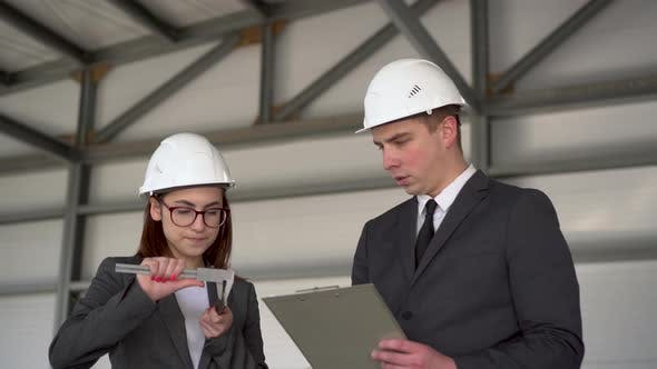 Thumbnail for Young Man and Woman in Helmets with Documents at a Construction Site. Businessmen in Suits Measure
