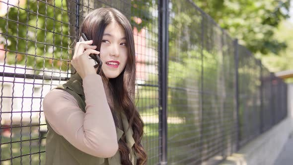 Thumbnail for Young Asian Woman Talks Smartphone Smile As She Leans Against Tall Fence