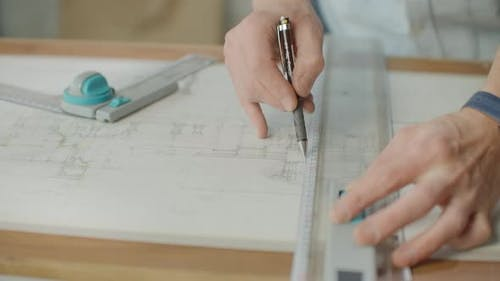 Close Up of Architect Hands Making House Blueprint in the Office Near Window