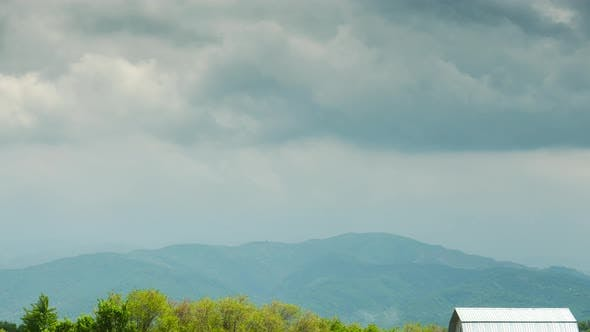 Thumbnail for Rural Timelapse with Rustic Cabins Against Mountains