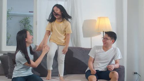 Happy young Asian family listen to music and dancing on sofa at home.