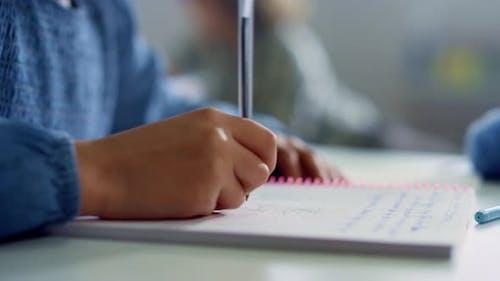Mädchen schreibt im Notizbuch am Schreibtisch im Klassenzimmer