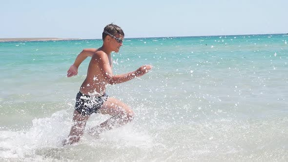 Teen Child Runs Across the Azure Sea and Falls Jumps Into the Water on a Sunny Day Slowmotion Video