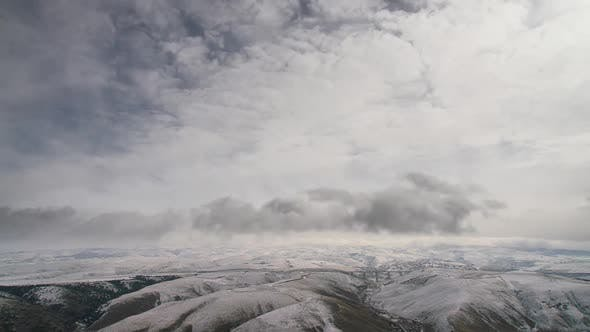 8K Cloud Movements in Patch of Snow Covered Winter Hills