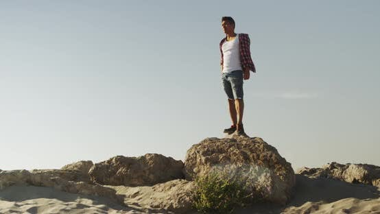 Thumbnail for Handsome Asian man standing on top of rock at the beach