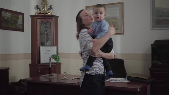 Thumbnail for Young Mother Standing in the Modern Office Room in Her Home Holding Baby Son in Arms