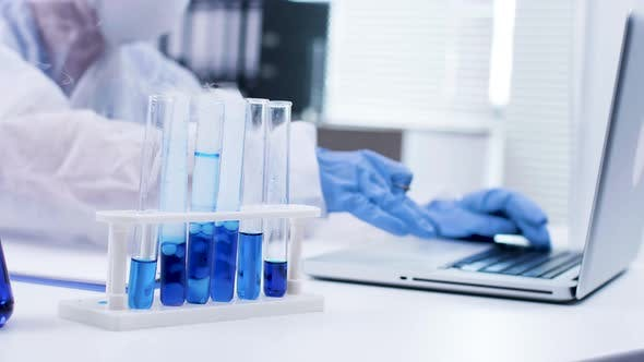 Close Up of Scientist Typing on Her Laptop and Smoking Blue Fluid in Test Tubes