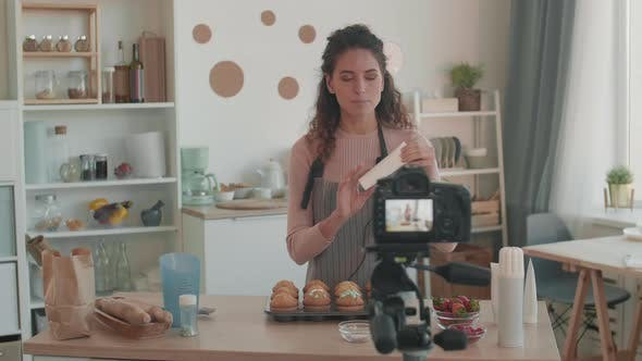 Woman Demonstrating Tube with Baking Icing