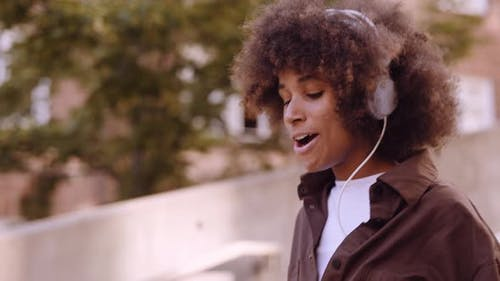 Woman Grooving To Music From Her Headphones As She Walks Along