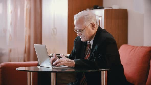 Thumbnail for Elderly Grandfather - Old Grandfather Is Typing on a Computer Then Displeasedly Putting His Glasses