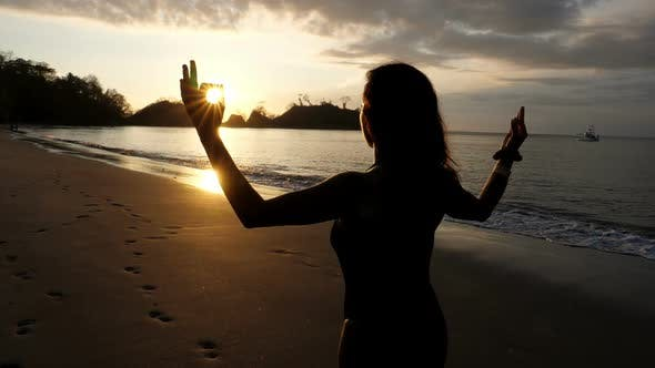 Cover Image for Young Girl Practicing Yoga on the Beach at Sunset