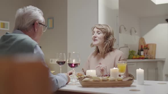 Joyous Elderly Couple Talking at Romantic Dinner