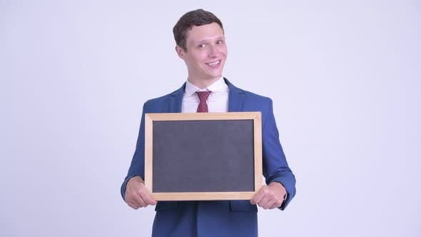 Thumbnail for Happy Young Businessman Holding Blackboard and Looking Surprised