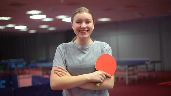 Porträt eines lächelnden jungen Mädchen-Tischtennisspielers mit einem Tischtennisschläger