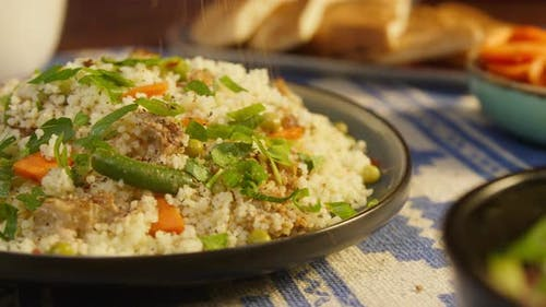 Sprinkling Pepper on Couscous with Chicken on Table Closeup